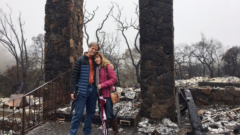 Birgit and Jeff Sengstack stand in front of the ruins of their home, burned down on October 9 when a
