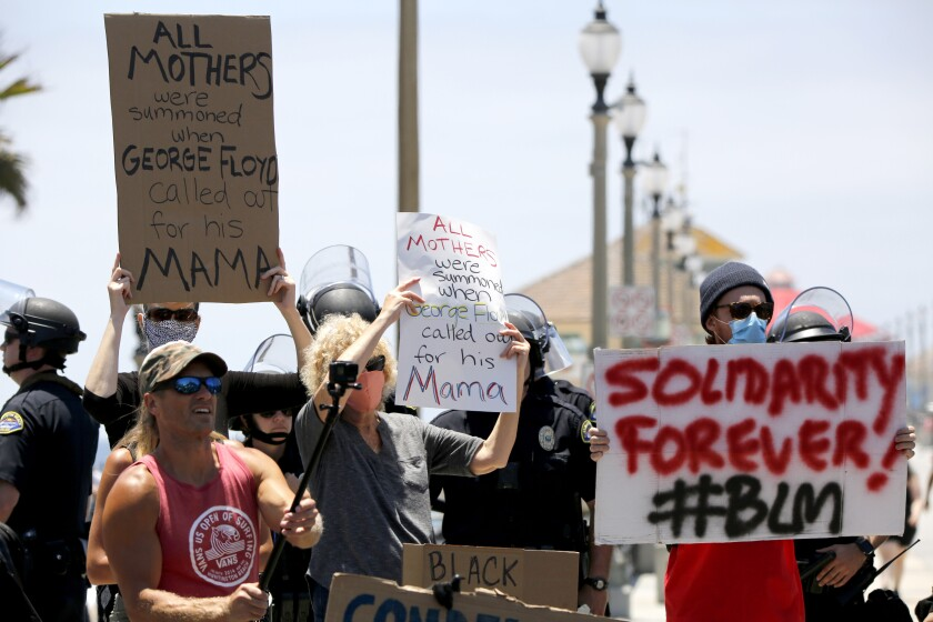 Protesters hold up signs during Saturday's protest in Huntington Beach.