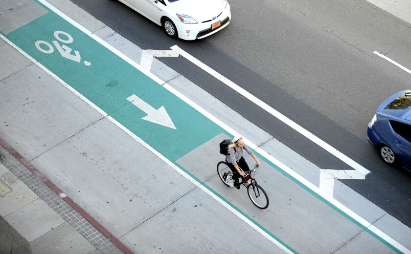 A cyclist uses a bike lane in downtown Los Angeles on Aug. 11.