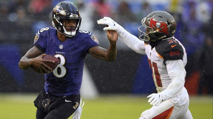 Baltimore Ravens quarterback Lamar Jackson, left, rushes against Tampa Bay Buccaneers free safety Jo