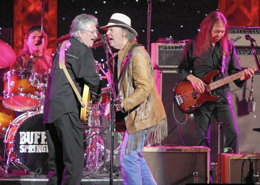 Longtime session musician Rick Rosas, right, here playing with Neil Young, center, Richie Furay and Joe Vitale during a Buffalo Springfield reunion concert in Los Angeles in 2011, has died at the age of 65.