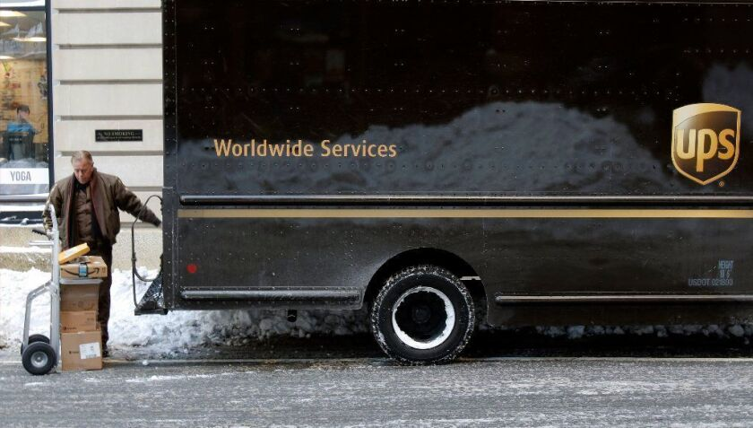 A UPS delivery driver loads his cart with packages from his truck Jan. 5 in Boston.