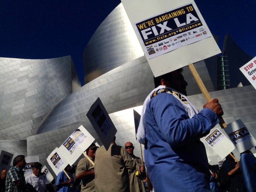 City workers and labor activists marched through the streets of downtown Los Angeles Oct. 28, demanding that city leaders step up pressure on Wall Street banks to renegotiate deals they say are costing the city.