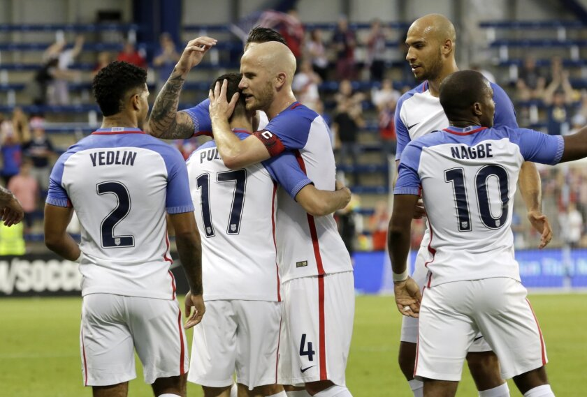 U.S. forward Christian Pulisic (17) is congratulated by his teammates after scoring against Bolivia in the second half of an international friendly soccer match, Saturday, May. 28, 2016, in Kansas City, Kan. (AP Photo/Colin E. Braley)