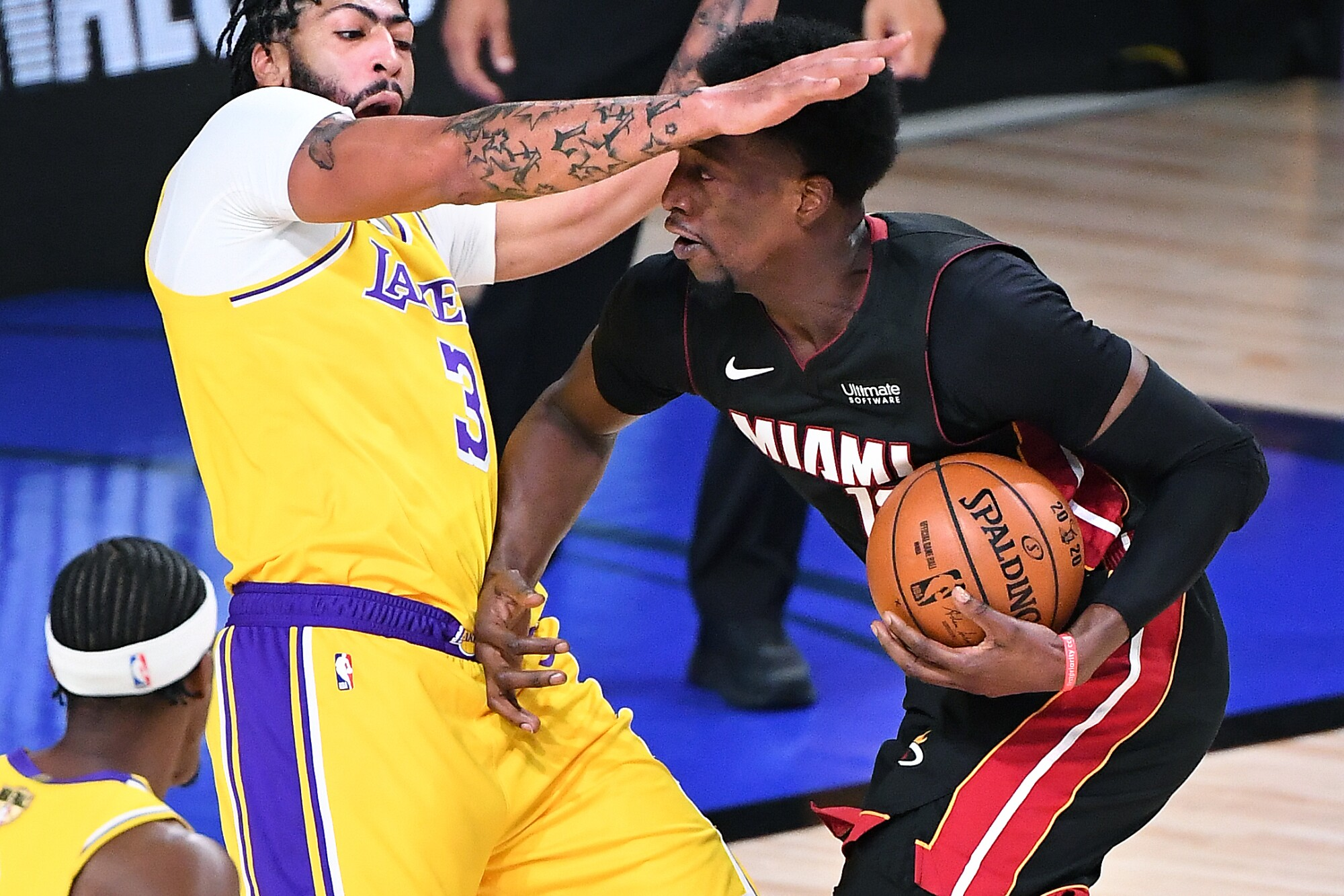 Lakers forward Anthony Davis takes a charge from Heat center Bam Adebayo during Game 4.