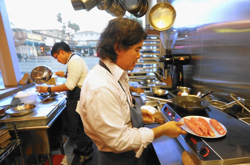 Chef Gary Menes, right, prepares Wagyu beef as part of his six-course tasting menu at Le Comptoir in the Hotel Normandie.