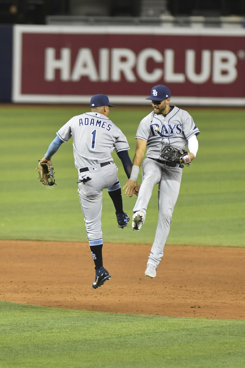 Tampa Bay Rays shortstop Willy Adames, left, and center fielder Kevin Kiermaier celebrate after defeating the Miami Marlins in a baseball game Friday, April 2, 2021, in Miami. (AP Photo/Gaston De Cardenas)