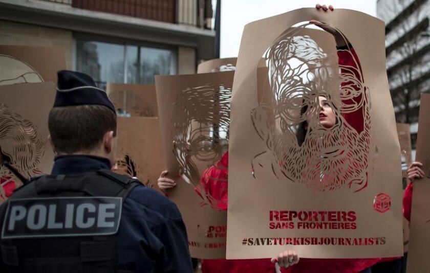 Activistas de la organización Reporteros Sin Fronteras (RSF) muestran retratos de periodistas turcos encarcelados durante una protesta ante la Embajada de Turquía en París (Francia). EFE/Archivo