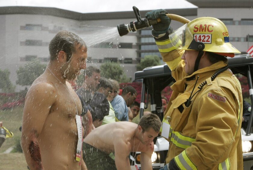 Chuck Kelly, acting as a radioactive bomb victim, is hosed off by San Marcos firefighter Robbie Richard. About 60 volunteers took part at CSU San Marcos.