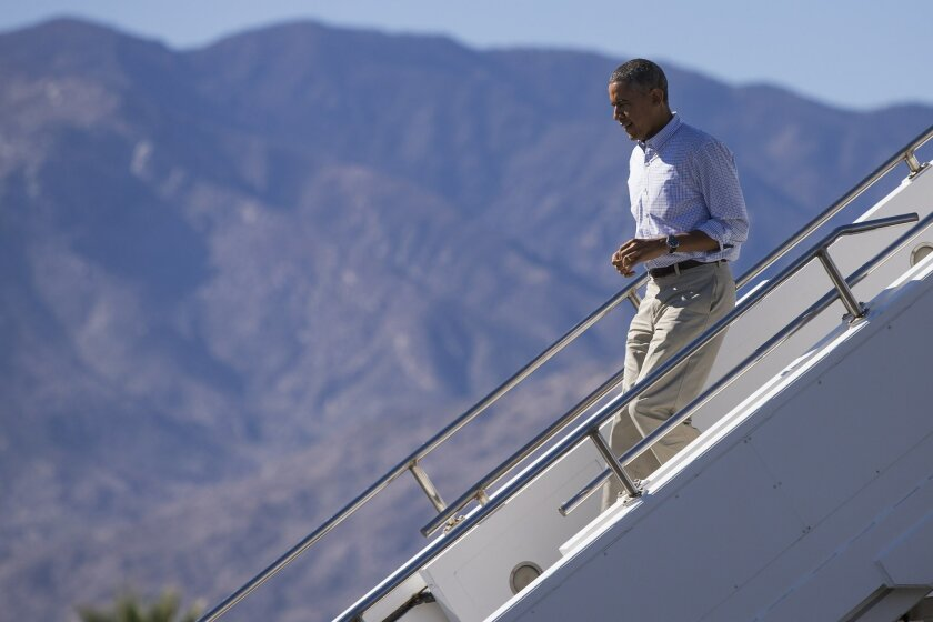President Barack Obama steps off Air Force One after arriving at Palm Springs International airport, on Saturday, Feb. 14, 2015, in Palm Springs, Calif. Obama is spending President's Day weekend playing golf in the area.