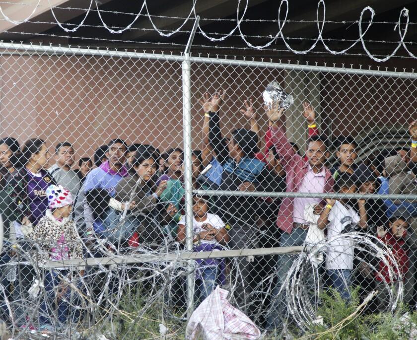 ARCHIVO - En esta fotografía de archivo del 27 de marzo de 2019, migrantes centroamericanos esperan comida en una zona cercada en El Paso, Texas. (AP Foto/Cedar Attanasio, Archivo)