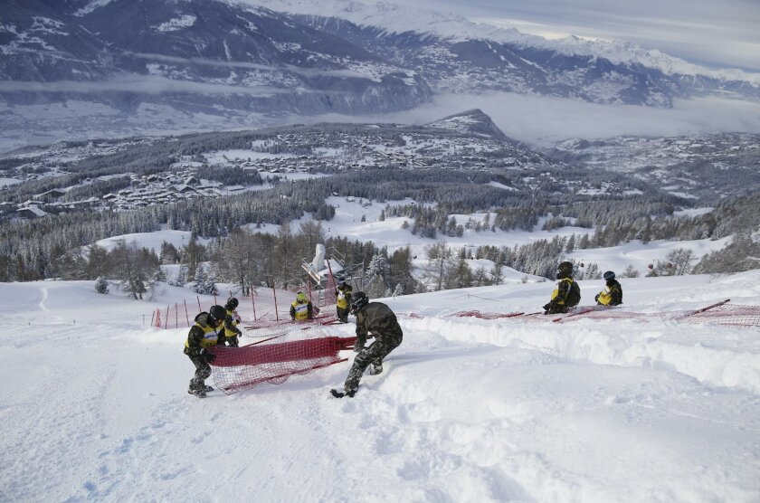 Soldiers and race officers  work on the track after an alpine ski, women's World Cup downhill race was canceled following a heavy snowfall, in Crans Montana, Switzerland, Saturday, Feb. 13, 20176. (AP Photo/Alessandro Trovati)