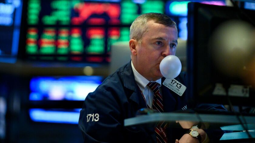 A trader chewing gum blows a bubble while working on the floor of the New York Stock Exchange.