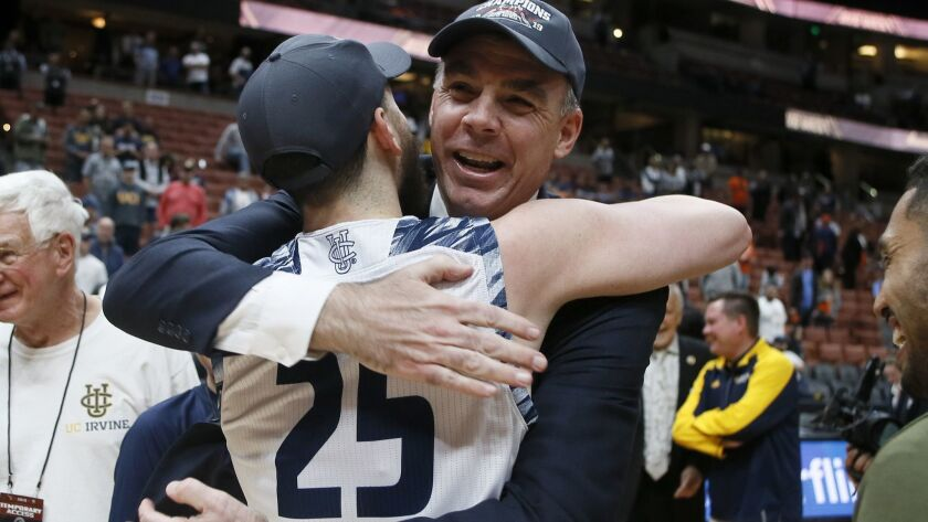 UC Irvine head coach Russell Turner, right, celebrates with guard Spencer Rivers (25) after their te