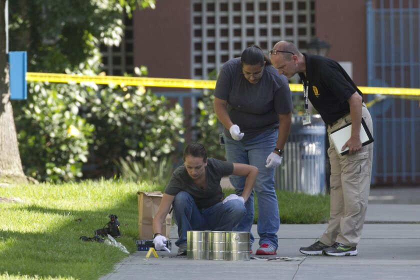 San Diego's Metro Arson Strike Team and SDPD homicide team gather evidence from the sidewalk and grassy area where a homeless person was attacked in downtown San Diego early Wednesday morning, July 6, 2016. It is the fourth attack on homeless men in San Diego in four days, two of which resulted in