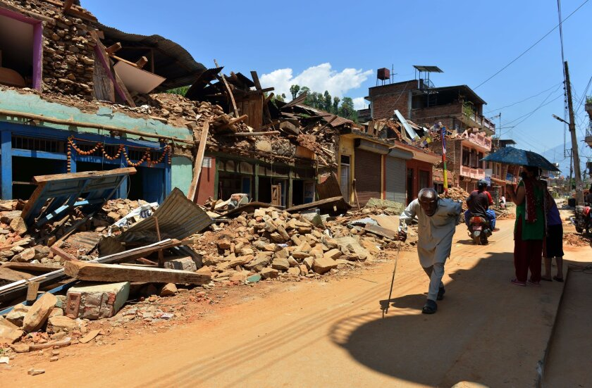 Nepalese people walk past damaged houses in Nuwakot district north of Katmandu on Monday. The earthquake death toll has risen to more than 7,200 with some 14,000 injured.