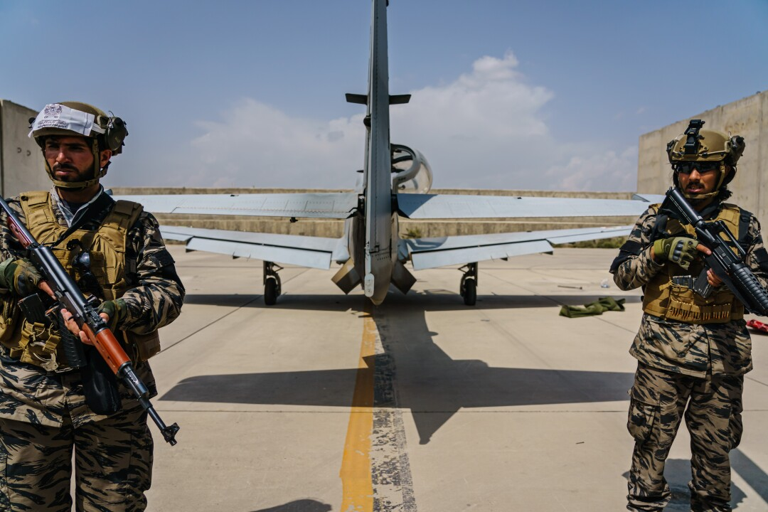 Taliban fighters with guns stand behind an airplane at Hamid Karzai International Airport