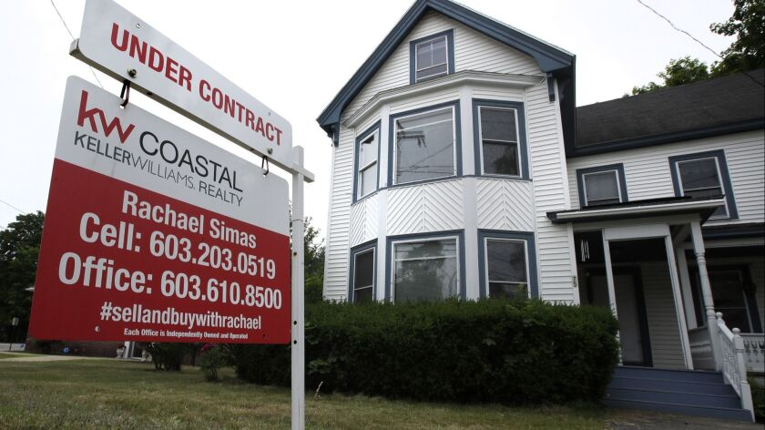 """FILE - In this June 20, 2018, file photo, an """"Under Contract"""" sign is displayed in front of home for"""