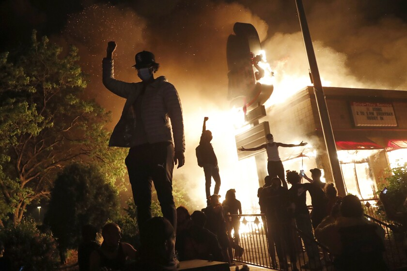 A protester stands, fist raised, in front of a burning fast food restaurant in Minneapolis.