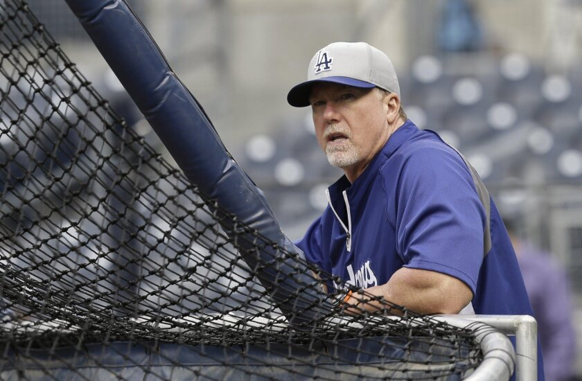 Los Angeles Dodgers batting coach Mark McGwire watches his team during batting practice before a baseball game against the San Diego Padres in San Diego on Thursday, April 11, 2013.