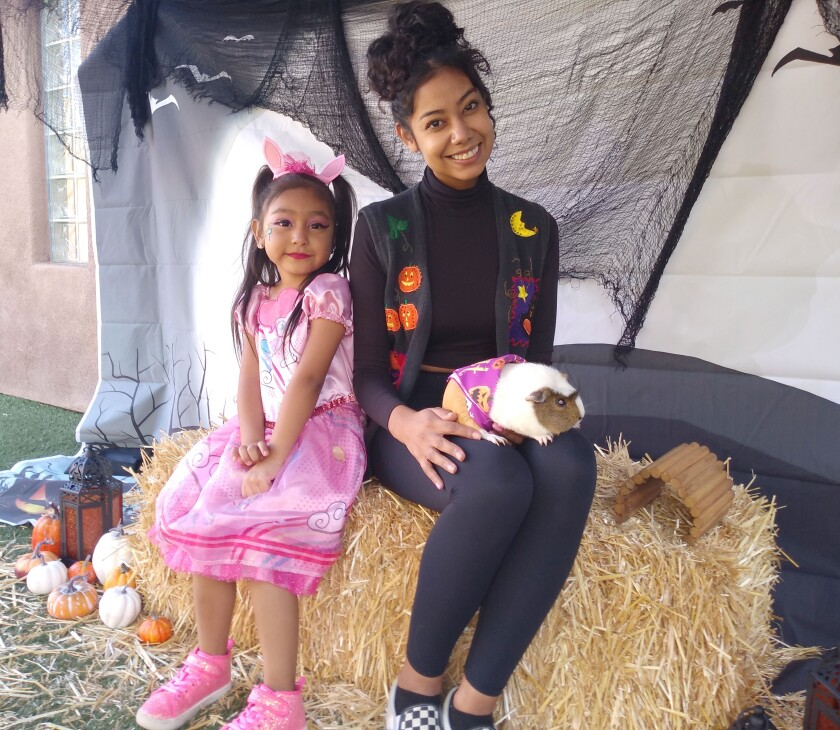 Adalia Sanchez, left, shows off her My Little Pony costume while her aunt, Lorena Sanchez, holds their guinea pig Gorda.