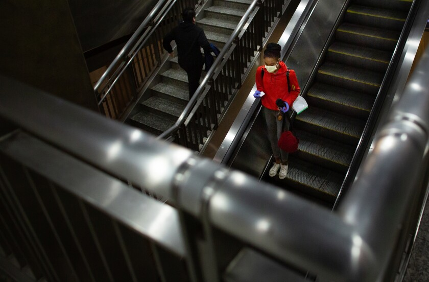 A woman wearing a mask rides the escalator in the Hollywood/Highland Metro Station on Thursday in Los Angeles.