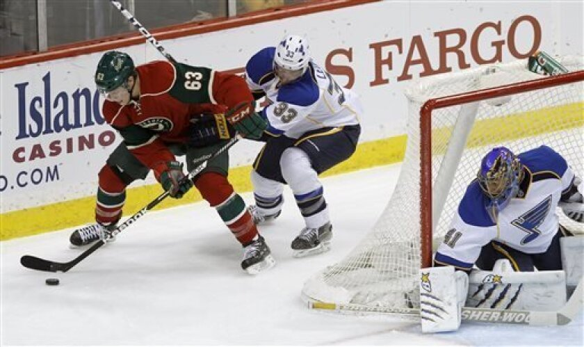 Minnesota Wild right wing Charlie Coyle (63) brings the puck around the net as St. Louis Blues defenseman Jordan Leopold (33) follows and St. Louis Blues goalie Jaroslav Halak (41) of Slovakia covers the net during the first period of an NHL hockey game in St. Paul, Minn., Monday, April 1, 2013. (A