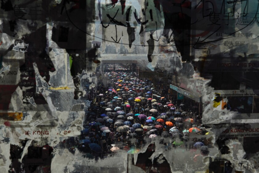 """Marching anti-government protesters are seen through a glass with peeled off posters , Tuesday, Oct. 1, 2019, in Hong Kong while the celebration of the People's Republic's 70th anniversary is taking place in Beijing. Police are warning of the potential for protesters to engage in violence """"one step closer to terrorism"""" during this week's National Day events, an assertion ridiculed by activists as propaganda meant to scare people from taking to the streets. (AP Photo/Vincent Yu)"""