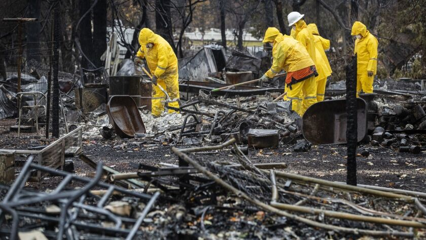 Recovery teams sift through the ashes looking for remains in the debris of a home in Paradise, Calif., during last week's rain.