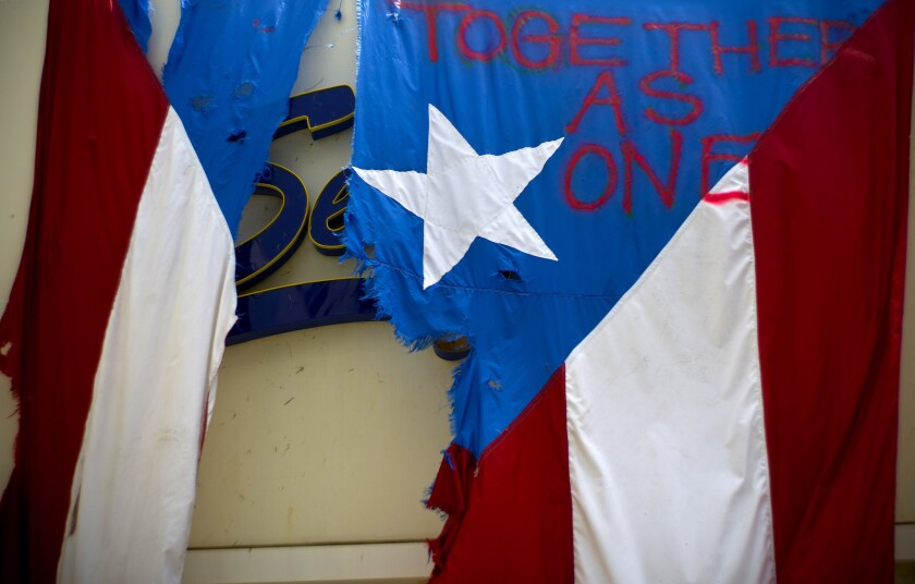 "FILE - In this Sept. 27, 2017 file photo, a ripped Puerto Rican national flag spray painted with the words ""Together as One"" hangs from the facade of a business, in San Juan, Puerto Rico. A federal control board that oversees Puerto Rico's finances filed in court Friday, Sept. 27, 2019, a long-awaited plan that it says would reduce the U.S. territory's debt by more than 60 percent and pull the island out of bankruptcy in what government officials called a historic moment. (AP Photo/Ramon Espinosa)"