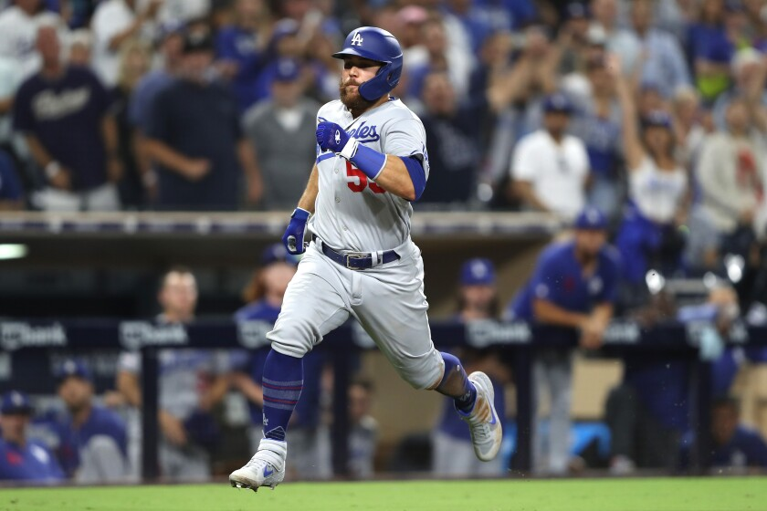 Dodgers catcher Russell Martin scores on an RBI single hit by outfielder A.J. Pollock during the tenth inning against the San Diego Padres on Wednesday in San Diego.
