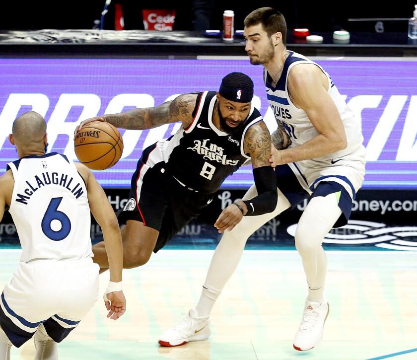 Clippers forward Marcus Morris Sr. drives to the basket against Timberwolves forward Juancho Hernangomez.