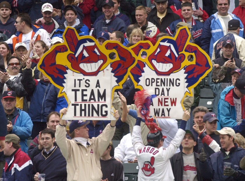 Cleveland Indians fans hold up Chief Wahoo logo signs in 2002.