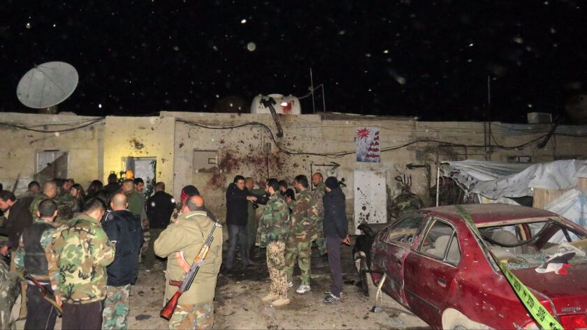 Syrian soldiers gather at the site of an attack on the western edge of the Syrian capital, Damascus.