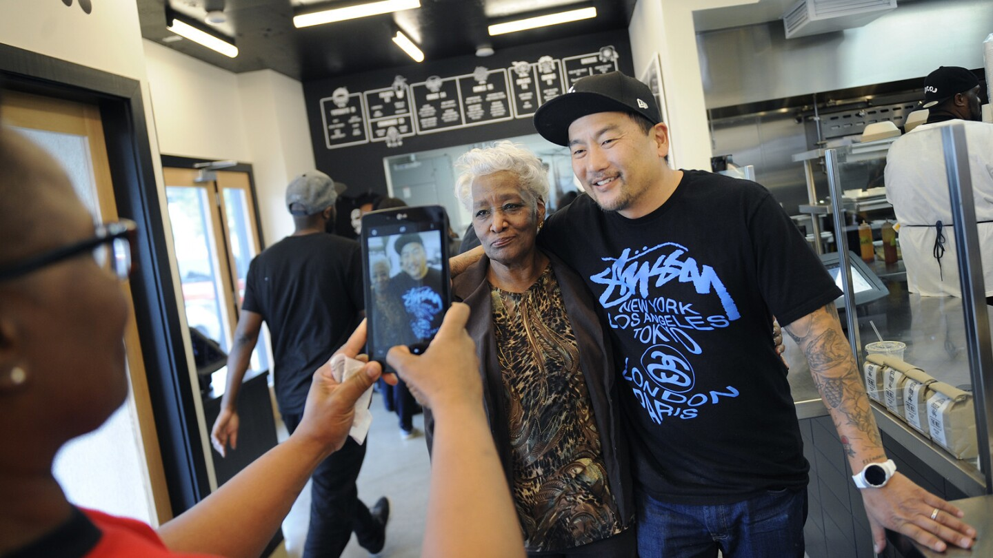 Tabitha O'Neal, left, takes a photo of her mother Delores, center, with Chef Roy Choi before dining at LocoL in Watts.