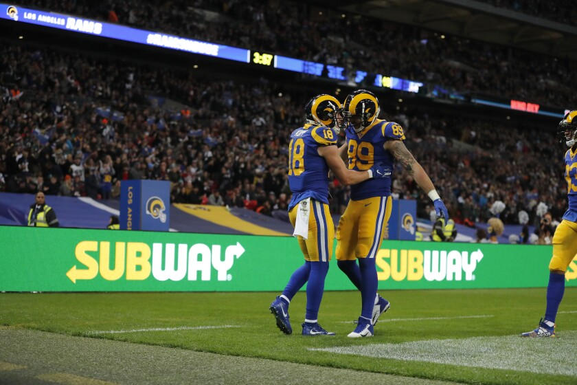 Rams receiver Cooper Kupp (18) is congratulated by tight end Tyler Higbee after scoring Oct. 27 against the Bengals at Wembley Stadium.