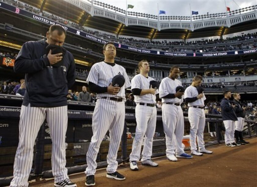 From left, New York Yankees relief pitcher Joba Chamberlain, starting pitchers Hiroki Kuroda, Phil Hughes, CC Sabathia and Andy Pettitte bow their heads during a moment of silence in honor of victims of the Boston Marathon explosions before a baseball game against the Arizona Diamondbacks at Yankee Stadium in New York, Tuesday, April 16, 2013. In big ways and small, New York is putting aside its heated and historical rivalry with Boston in a show of support after the Boston Marathon explosions.