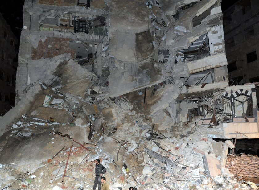 A handout photograph made available by the Syrian Arab news agency shows a residential building following an airstrike Sunday in Jaramana, Syria, that killed a Hezbollah operative.