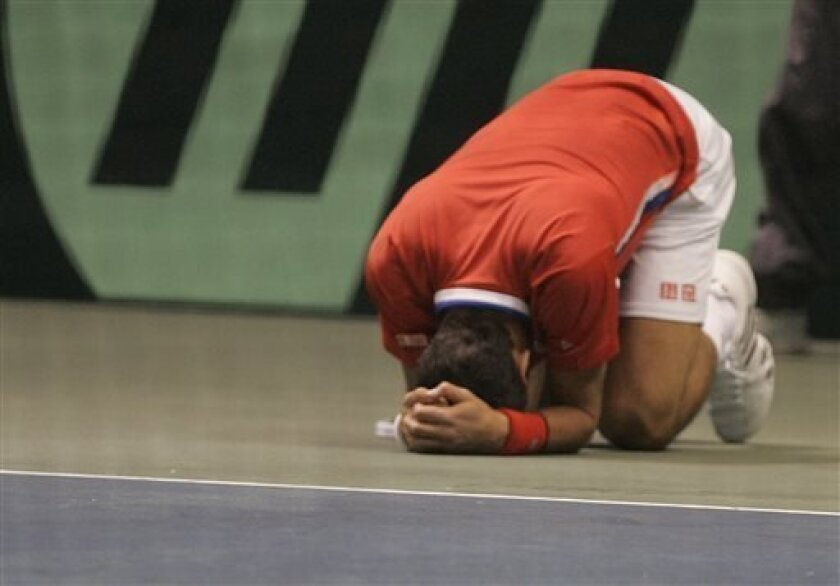 Novak Djokovic, of Serbia, goes down after turning an ankle against Sam  Querrey during the Davis Cup tennis tournament on Sunday  April 7, 2013, in Boise, Idaho. (AP Photo/Matt Cilley)