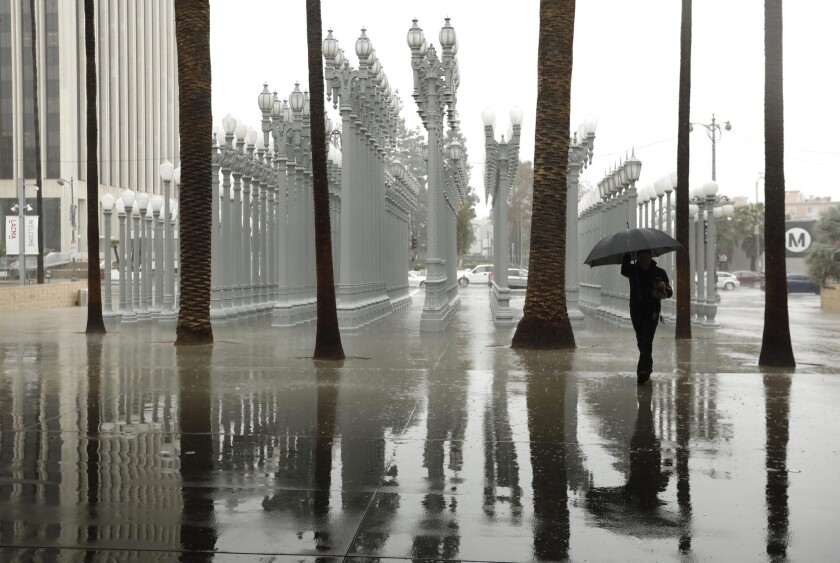 """A visitor to the Los Angeles County Museum of Art makes his way through the rain and walks by Chris Burden's sculpture """"Urban Light"""" during an atmospheric river storm in February 2019. The first atmospheric river of 2020 will make its way to L.A. next week."""