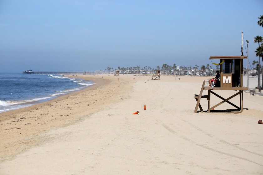 A city lifeguard keeps an eye on the few visitors to the beach next to the Balboa Pier in Newport Beach on May 6.