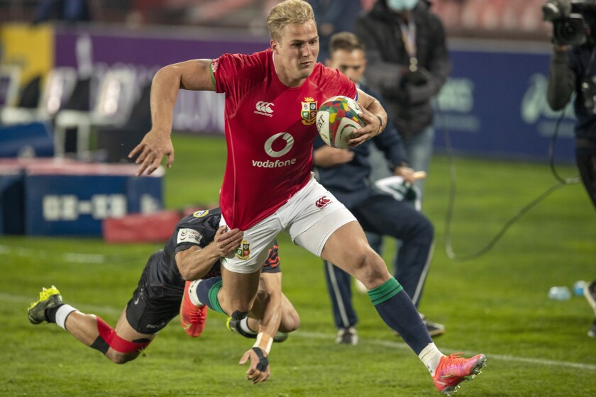 British and Irish Lions' Duhan van der Merwe, left, avoids a tackle from South African Sharks' Thaakir Abrahams to score a try during a warm-up rugby match between South Africa's Sharks and British and Irish Lions at Ellis Park stadium in Johannesburg, South Africa, Wednesday, July 7, 2021. (AP Photo/Themba Hadebe)