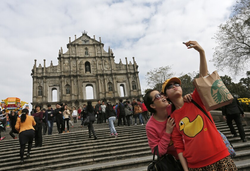 """FILE - In this Feb. 1, 2014, file photo, tourists take selfies at """"The Ruins of St. Paul's"""" a famous tourist spot, in Macao. Macao authorities ordered the closure of various entertainment venus and will test its population for the coronavirus after the city confirmed four new infections, authorities said Wednesday, Aug. 4, 2021. (AP Photo/Vincent Yu, File)"""