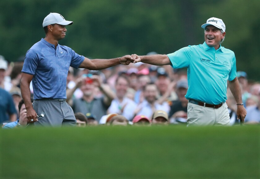 Tiger Woods and Fred Couples exchange a fist bump after they both hit their tee shots close to the cup on the par-3 12th hole at Amen Corner while playing a practice round for the Masters at Augusta National Golf Club on Monday in Augusta, Ga.