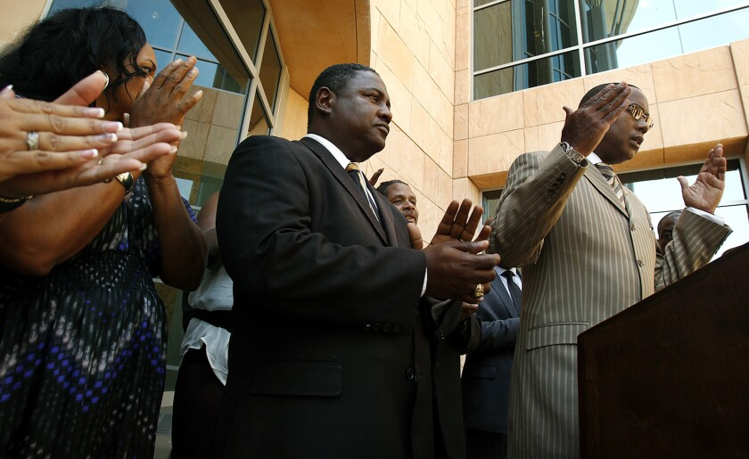 Stan Muhammad, far right, speaks during a press conference in July 2013 held by local civil rights groups including the Community Action League, National Assn. for the Advancement of Colored People, and League of United Latino American Citizens, in response to the Justice Department finding that Los Angeles County Sheriff's Department deputies in the Antelope Valley harassed and intimidated black, Latino and Section 8 residents.