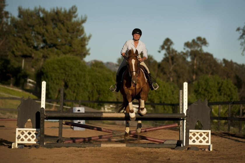 America Morris, who won five jumping titles last year, practices at Silver Sunset Farms in Bonsall.