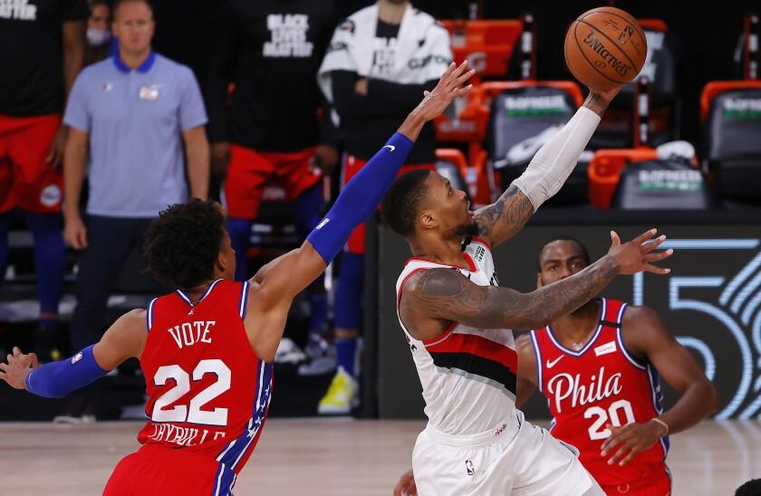 Portland Trail Blazers' Damian Lillard shoots next to Philadelphia 76ers' Matisse Thybulle, left, during the fourth quarter of an NBA basketball game Sunday, Aug. 9, 2020, in Lake Buena Vista, Fla. (Kevin C. Cox/Pool Photo via AP)
