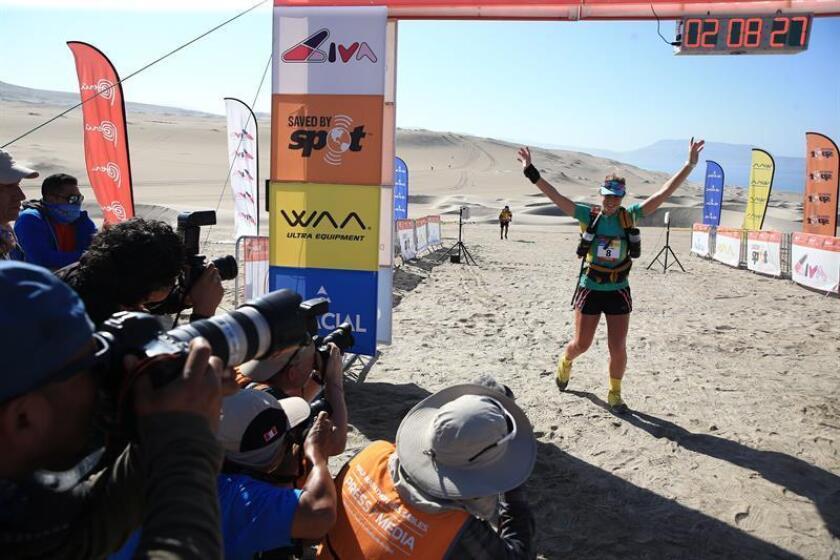 La atleta francesa Gaëlle Decorse fue registrada este jueves al celebrar su victoria en la tercera etapa del Medio Maratón de las Arenas de Perú, en el desierto de la región sureña de Ica (Perú). EFE