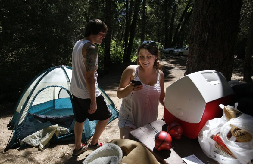 | Jordan Walker, left, jokes with his friend Shannon Price as she searches her iPod for just the right music to go with a recent camping trip on Palomar Mountain.
