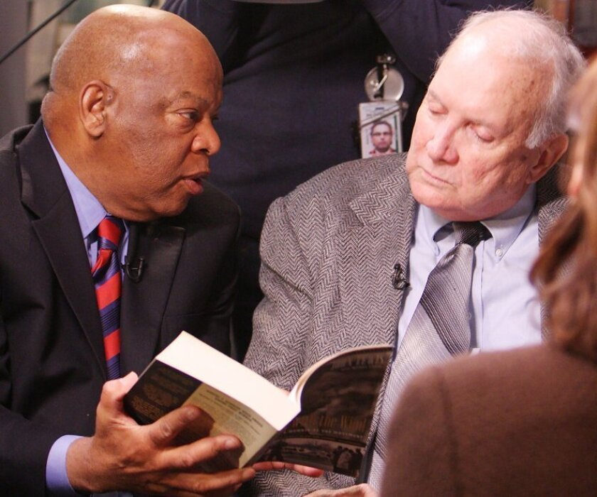"""U.S. Rep. John Lewis, D-Ga, left, gives Elwin Wilson of Rock Hill, SC a copy of Lewis' book in Lewis' Washington, D.C. office while taping an interview for """"Good Morning America."""" Wilson, part of a white gang in 1961 that jeered Lewis, attacked him and left him bloodied on the ground in South Carolina, met with Lewis in his Capitol Hill office so he could apologize to Lewis and express regret for his hatred."""